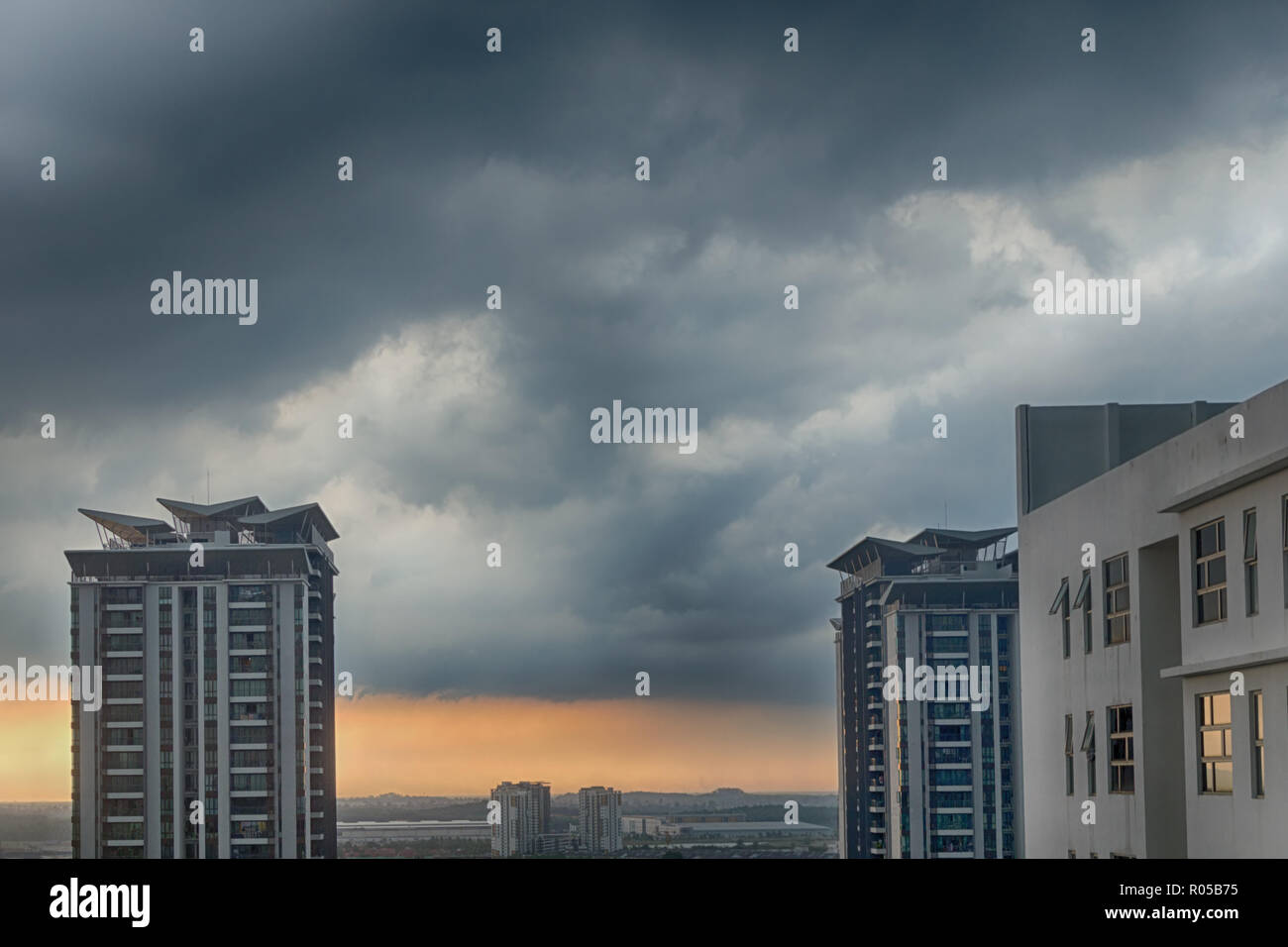 Stormy and rainy sunset Cyberjaya, Malaysia. Heavy rainy clouds over city. Tropical cyclone in asia. - Stock Image