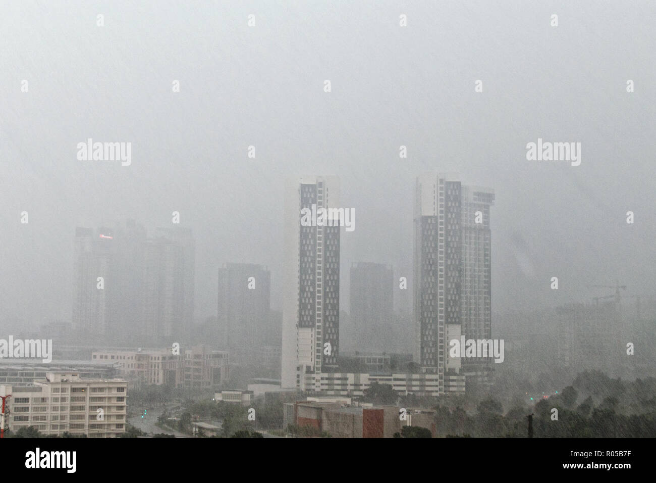 Top view of blurred city during rainy weather, rain stripes on background of skyscrapers, urban view on gray day. - Stock Image