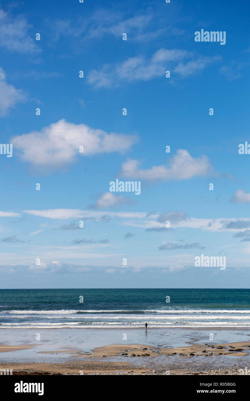 Distant figure on the beach at Crackington Haven, Cornwall, England, UK - Stock Image