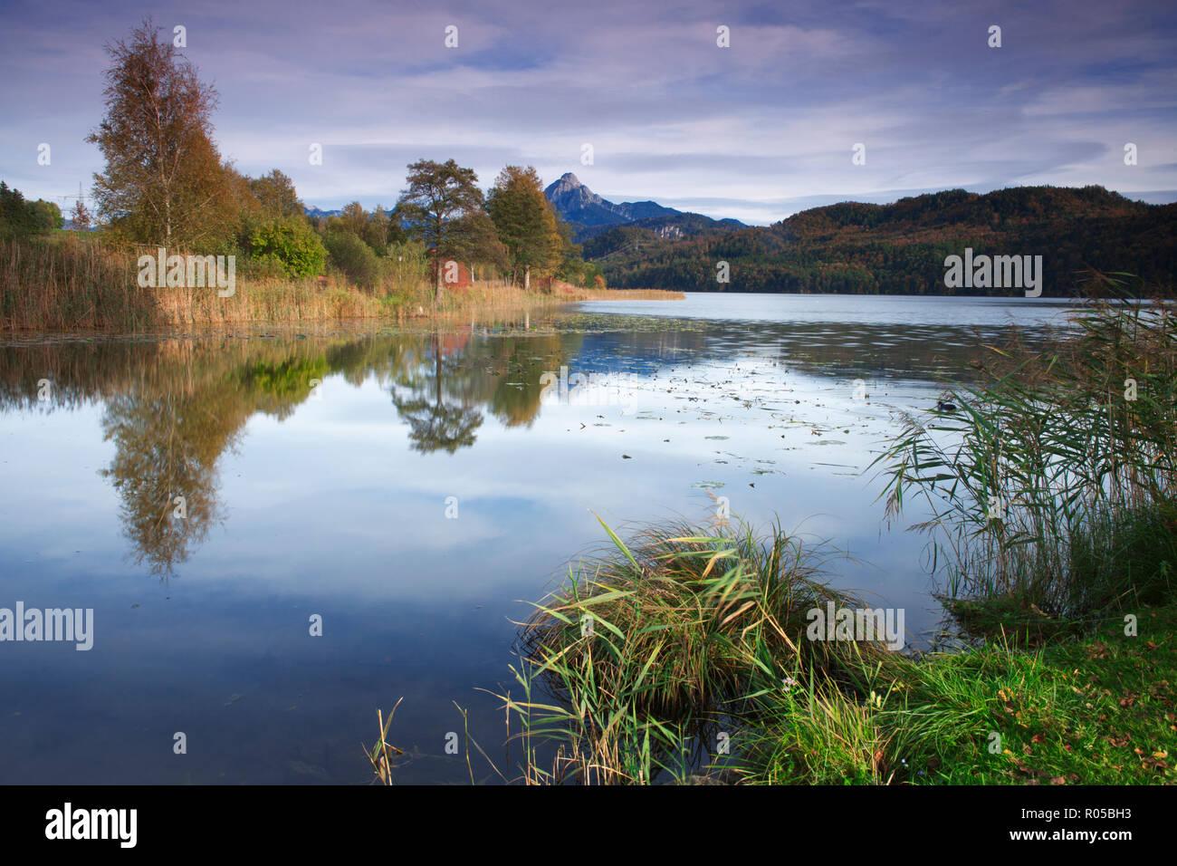 Langzeitbelichtung einer Landschaftsansicht des Weissensee in Bayern umrandet von herbstlichen Laubbäumen. Im Hintergrund ragt der Gipfel des Säulings Stock Photo