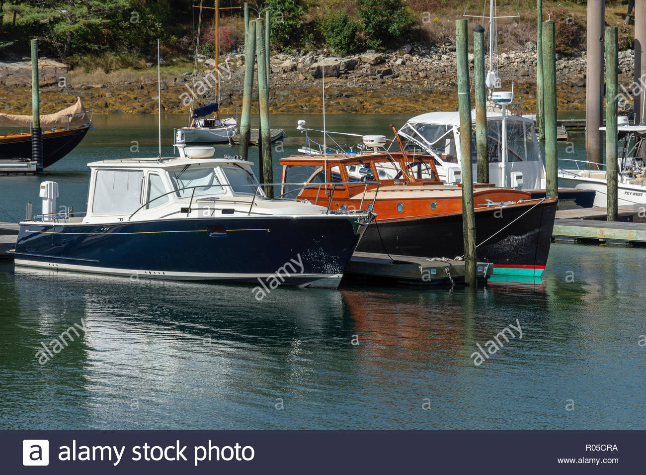 Northeast Harbor, Maine, USA - September 22, 2018: Older and newer style powerboats in adjoining slips in Northeast Harbor on last day of summer - Stock Image