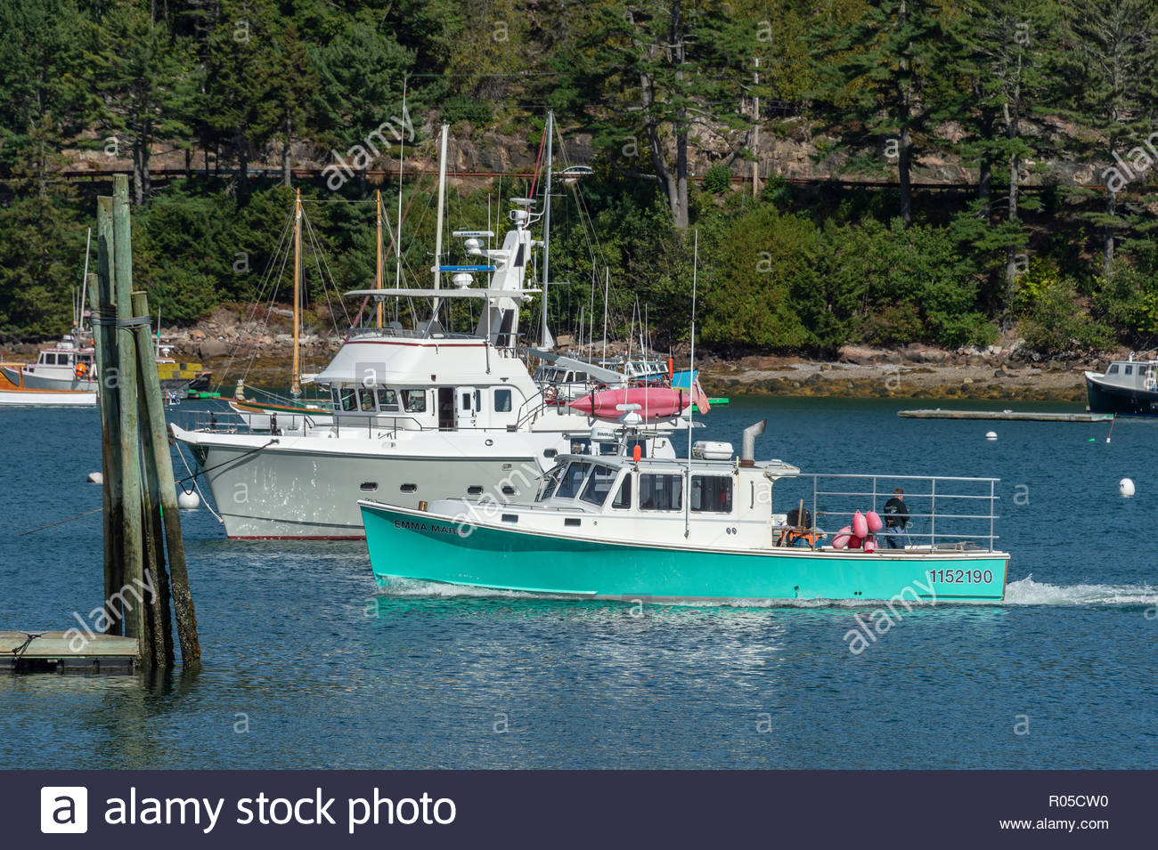 Northeast Harbor, Maine, USA - September 22, 2018: Lobster boat Emma Marie cruising past motor yacht in Northeast Harbor on last day of summer - Stock Image