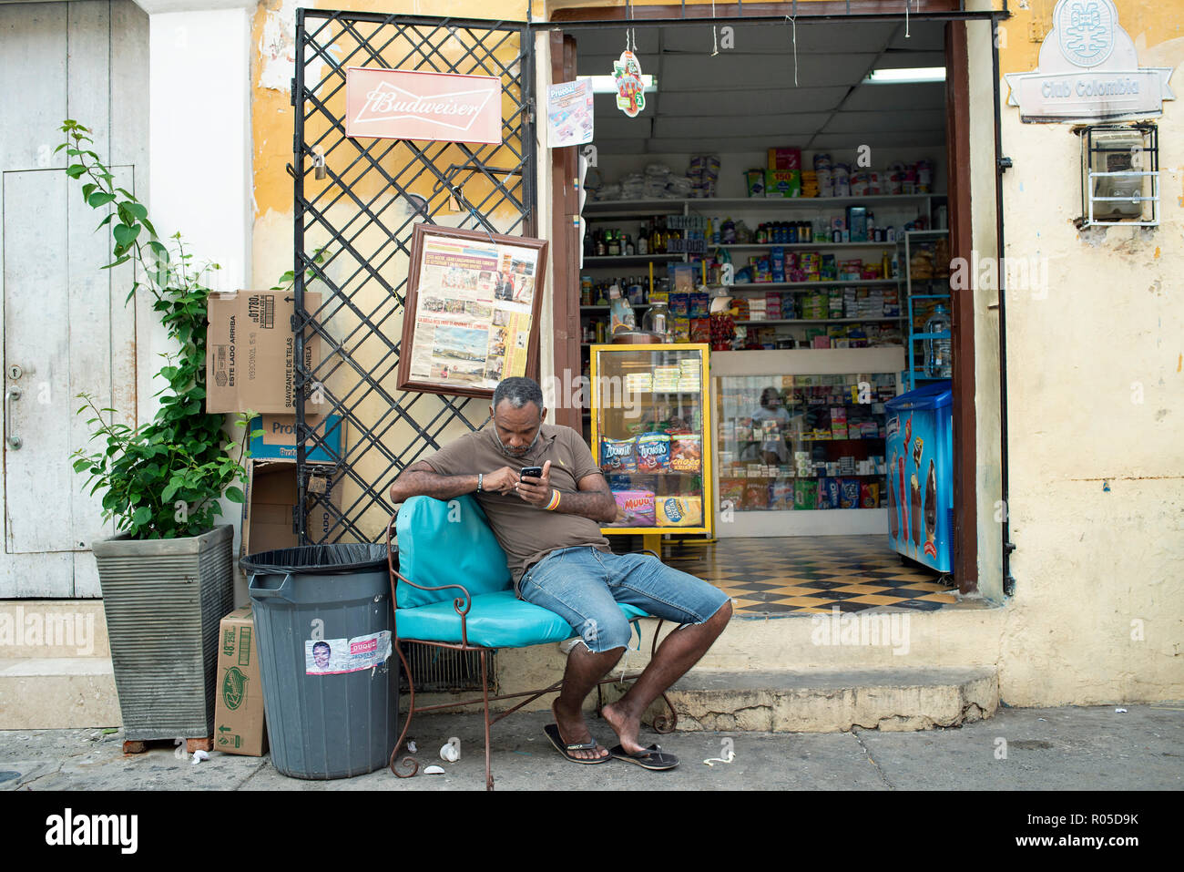 Unidentified Colombian man sits outside his shop in Getsemani, checking his mobile phone. Cartagena de Indias, Colombia. Oct 2018 Stock Photo