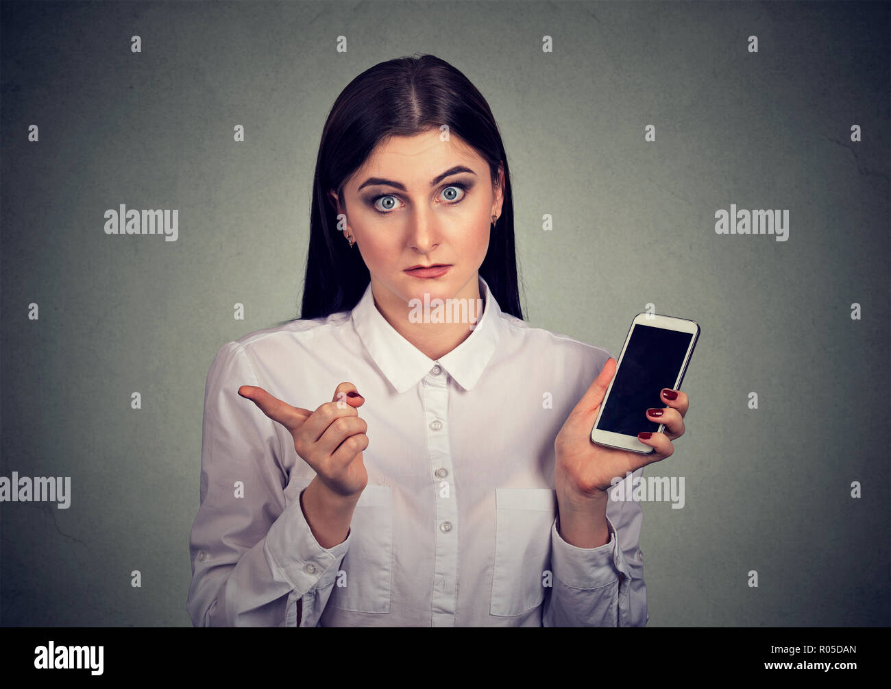 Formal irritated woman in white shirt holding smartphone and shaking with finger giving bad review on gray background - Stock Image