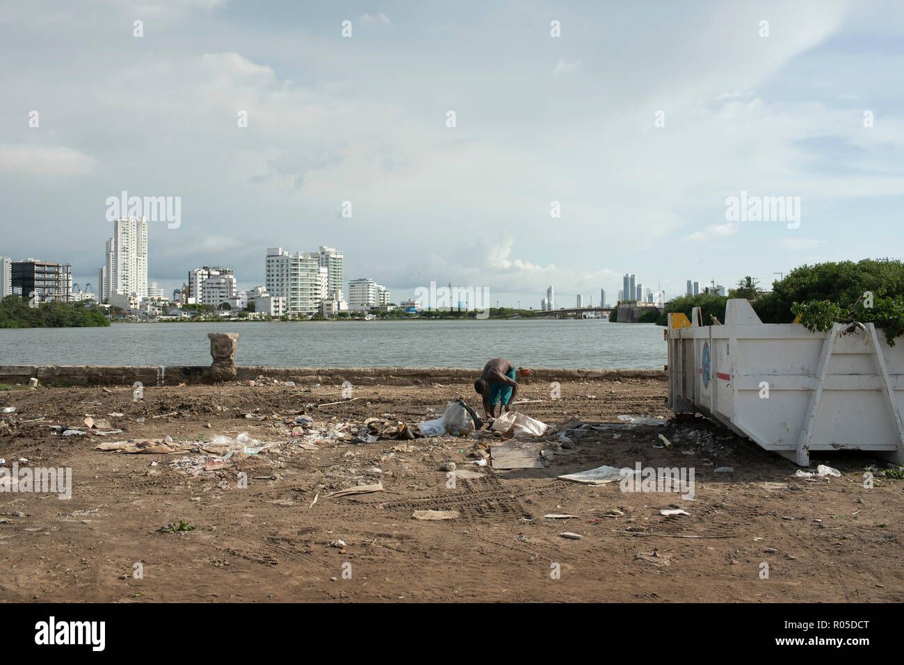 Juxtaposition of rich and poor. Young African man searches through rubbish with shiny new buildings in the background. Cartagena, Colombia. Sep 2018 - Stock Image