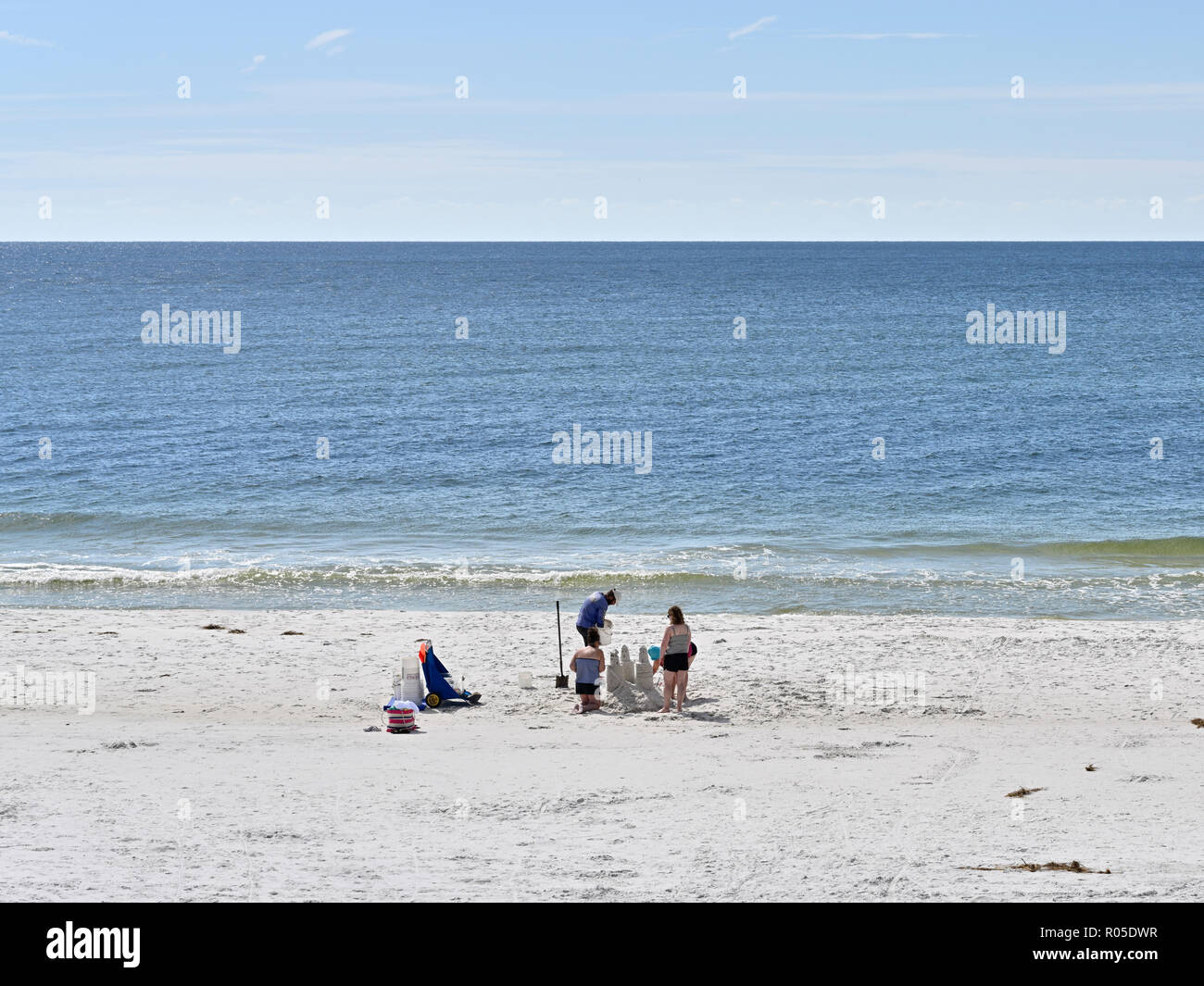 Family building a sand castle on the Florida beach at Deer Lake State Park, Florida USA. Stock Photo