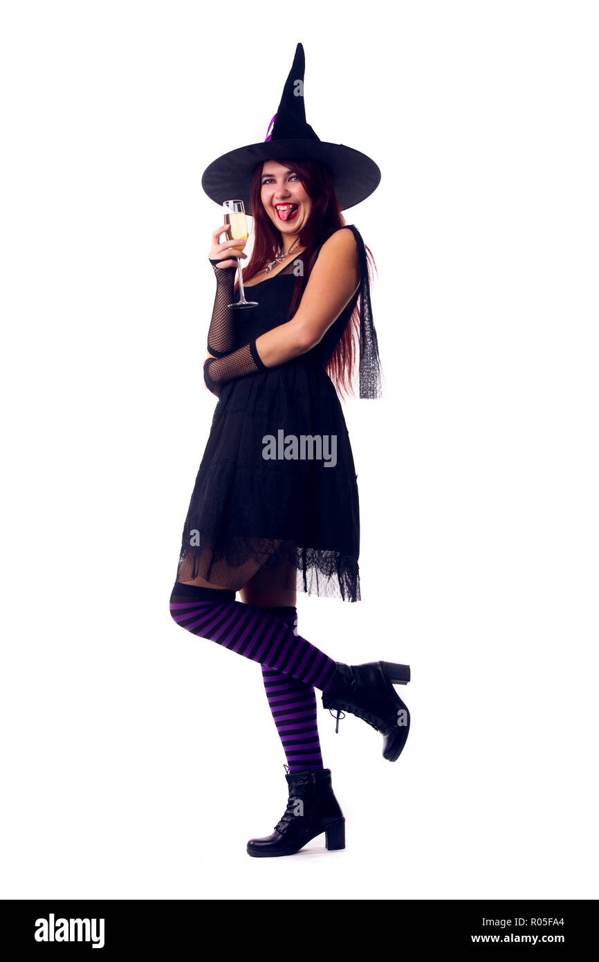 Photo of smiling witch brunette in black dress and hat - Stock Image