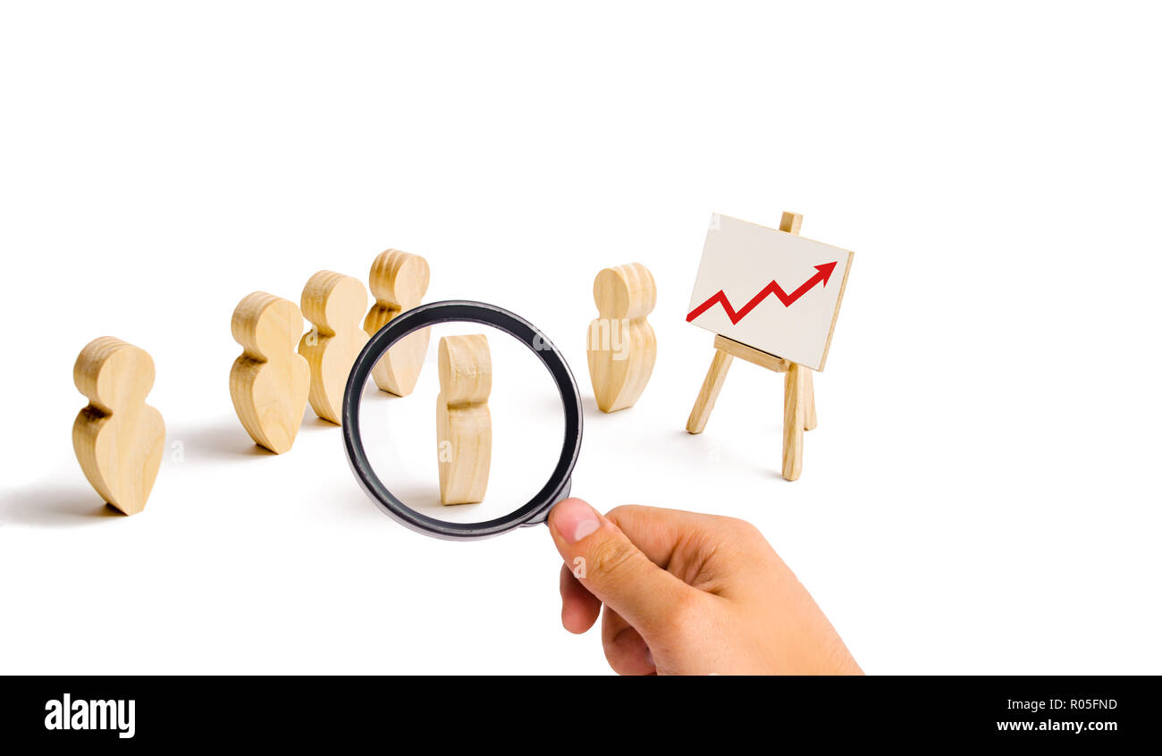 Magnifying glass is looking at the Wooden figures of people stand in the formation and listen to their leader. Business training, briefing and inspira - Stock Image