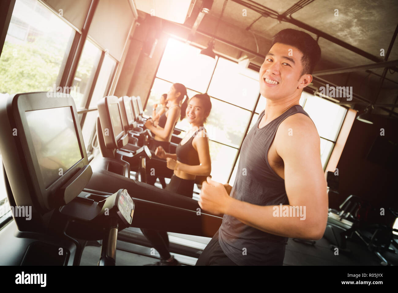 Happy asian young man with group of young people running or jogging on treadmills in modern sport gym. exercise and sport concept. - Stock Image