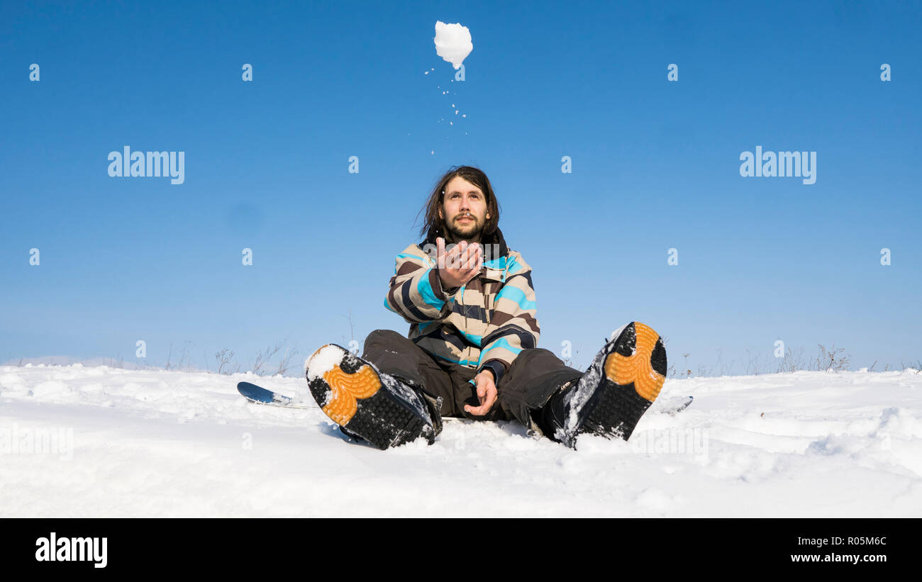 Snowboarder with a long hair sitting on a snowboard and throw a snowball in the air. Extreme winter sport. - Stock Image