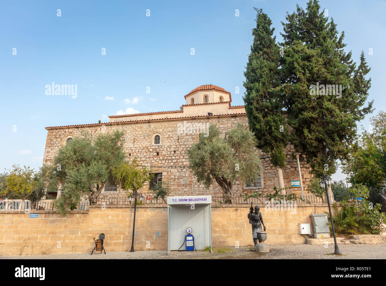 Street view of historic mosque in Dydim near the Temple of Apollo with electric mobility charging station and statue of water seller. - Stock Image