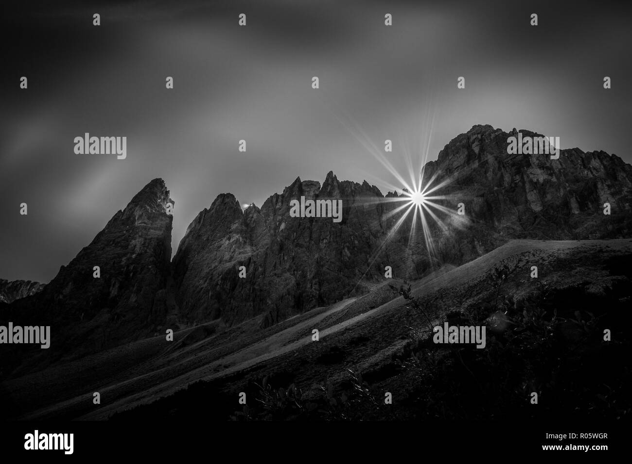 Black and white effect of morning sun rising above Cima Una dolomite peaks South Tyrol, Italy - Stock Image