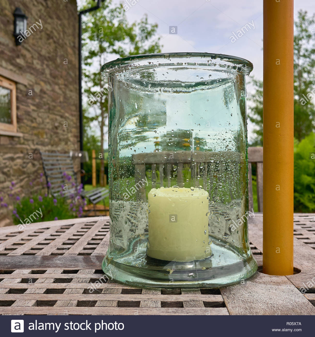 a large white unlit candle inside a glass jar covered with rain drops on a wooden patio outside in a british uk garden Stock Photo