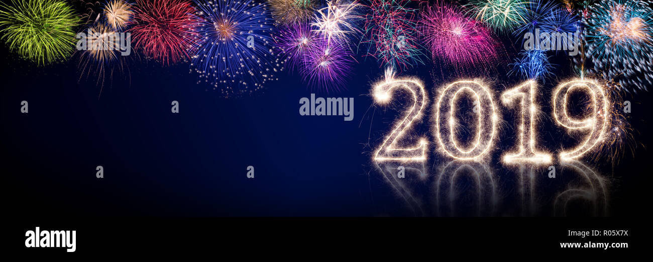 colorful fireworks and bright sparkler pyrotechnic number 2019 happy new year sylvester concept on black blue panorama background - Stock Image