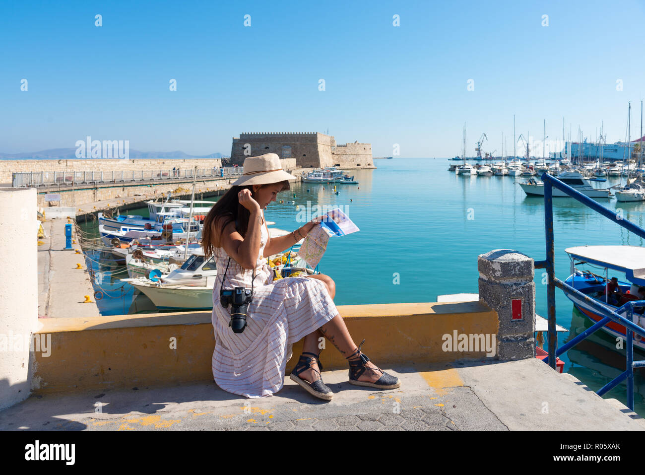 Travelling tourist woman on vacation in Heraklion Crete walking at the port. Lovely elegant girl in beige dress visiting the famous Mediterranean Vene - Stock Image