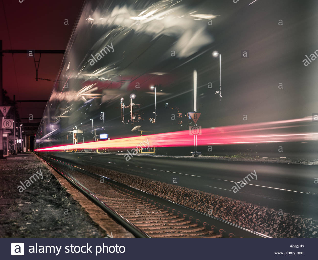 Long exposure shot of a passenger train passing tru a train station at night. Impression of  a train due to transparency, reflections and light trails - Stock Image