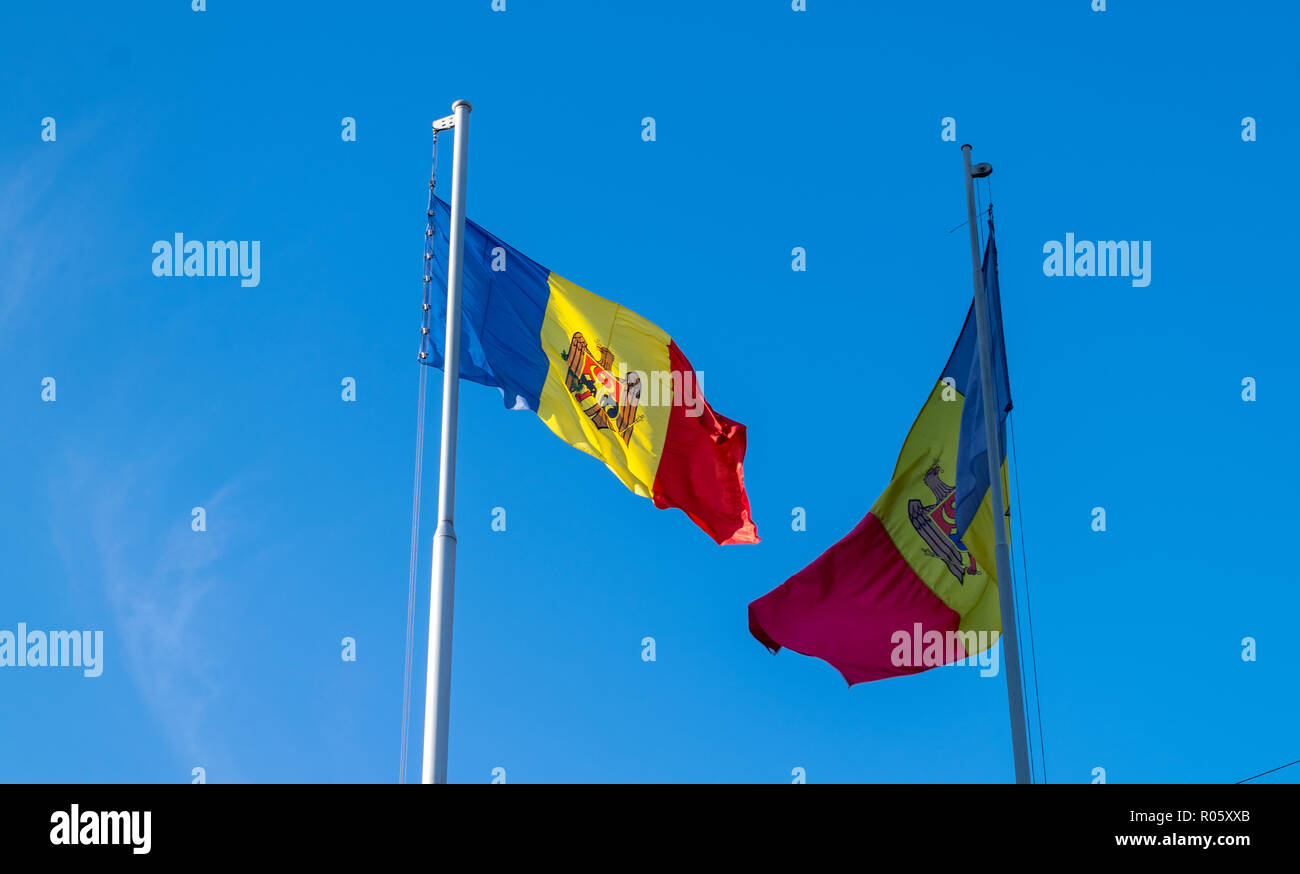Two moldavian flags flutter in the blue sky. - Stock Image