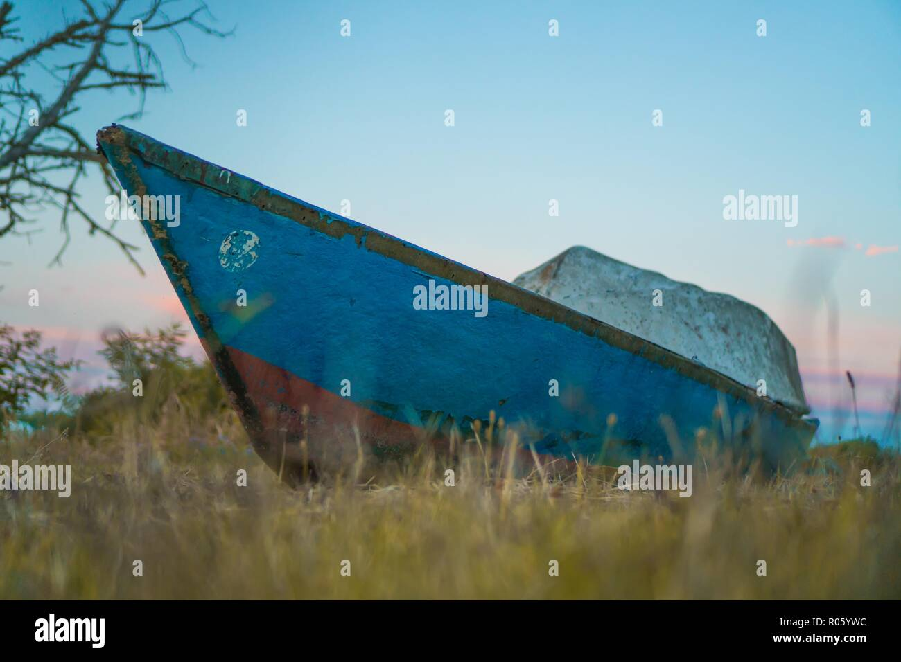 A small antique wooden boat resting on the yellow grass - Stock Image