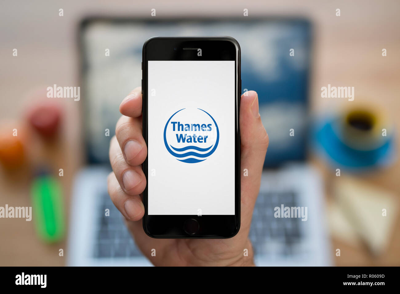 A man looks at his iPhone which displays the Thames Water logo, while sat at his computer desk (Editorial use only). - Stock Image