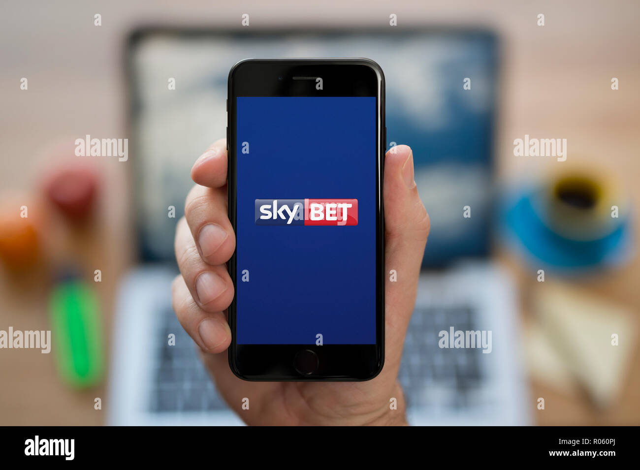A man looks at his iPhone which displays the Sky Bet logo
