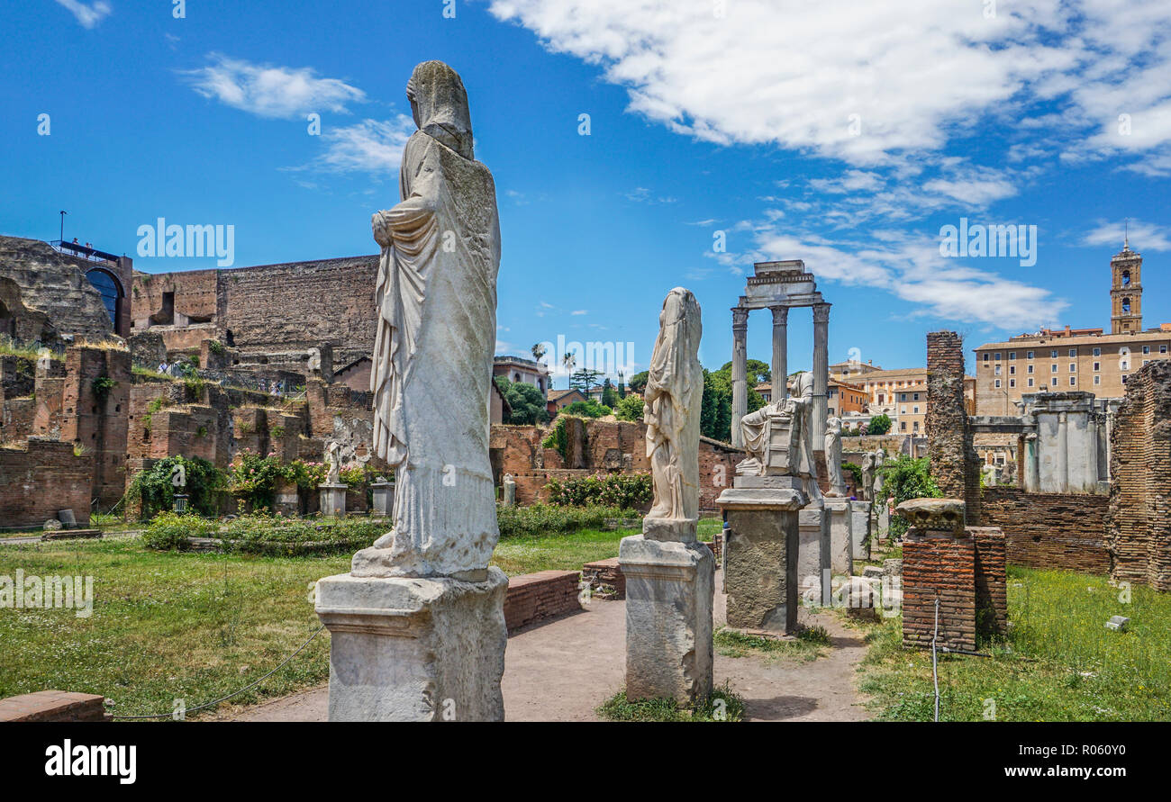 Roman statues at the site of the House of Vestals in the Roman Forum with the three remaining Corinthian columns of the Temple of Castor and Pollux in - Stock Image