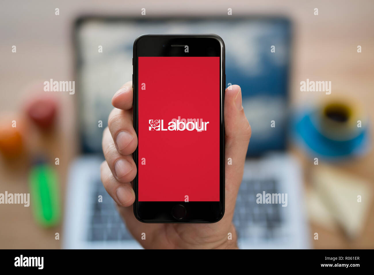 A man looks at his iPhone which displays the Labour Party logo, while sat at his computer desk (Editorial use only). - Stock Image