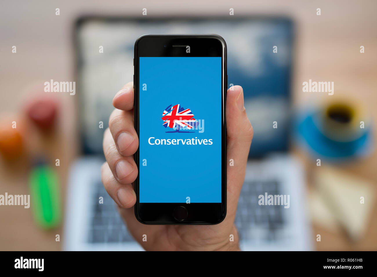 A man looks at his iPhone which displays the Conservative Party logo, while sat at his computer desk (Editorial use only). - Stock Image