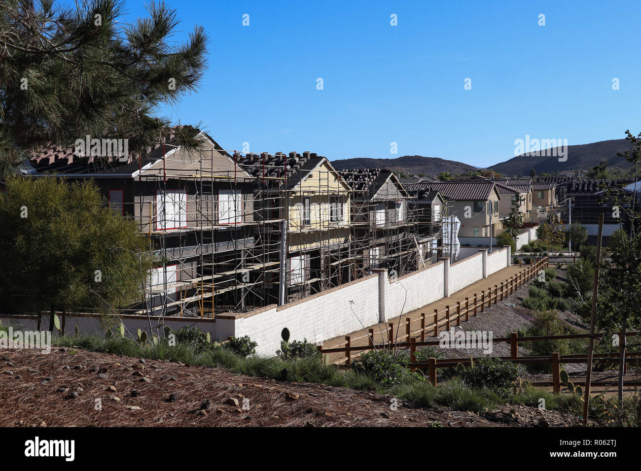 Four new family homes under construction and surrounded by scaffolding in a suburban neighborhood with public trails, fencing, copy space in blue sky Stock Photo