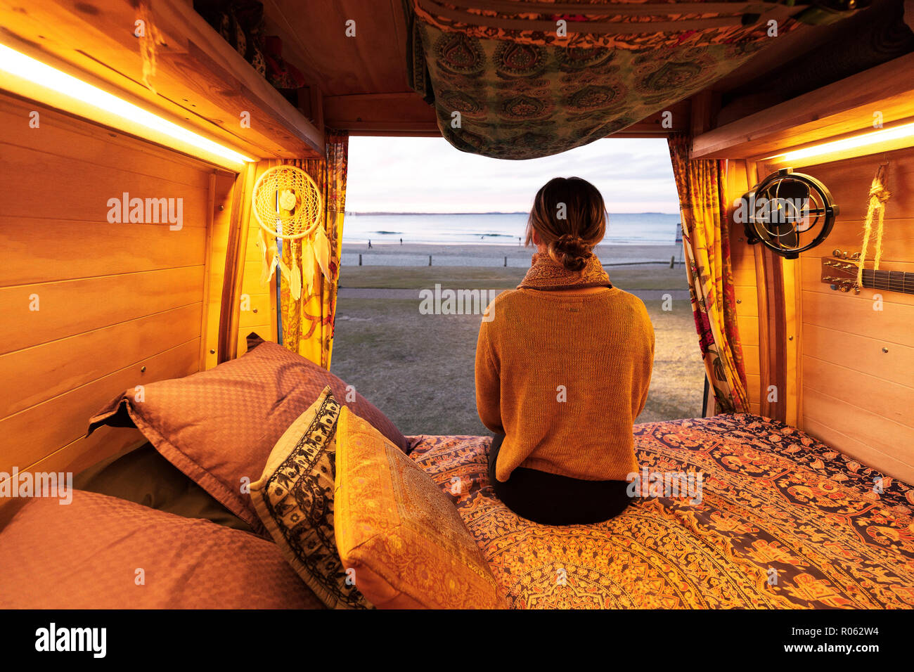 Woman watching sunset over beach from bohemian camper van in a van life theme Stock Photo