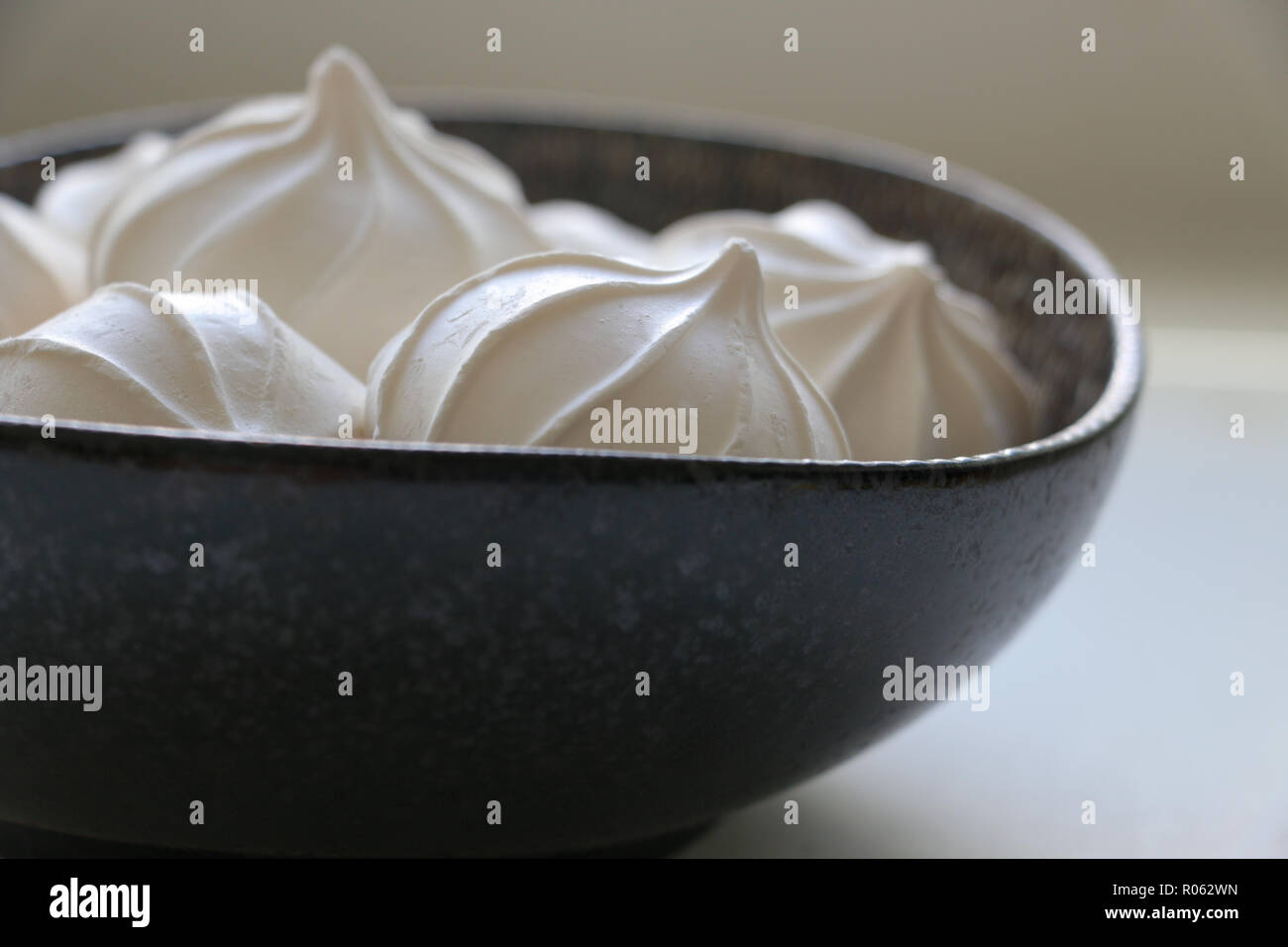Close-up of a black bowl filled with white meringues just peeking out of the top in diffuse natural window light; a nice nibble for tea time. - Stock Image