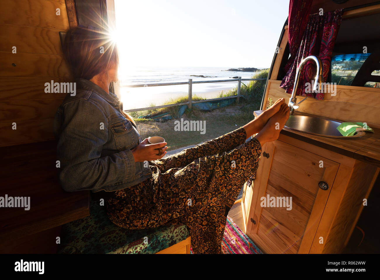 Young woman in camper van, van life theme at sunrise by the beach Stock Photo