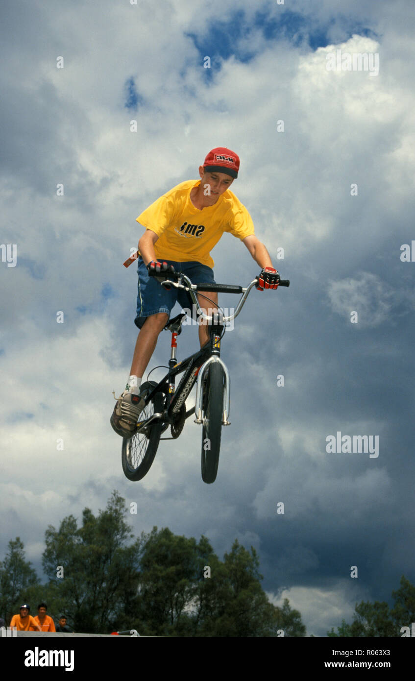 Young boy performing stunts on BMX bike without wearing safety helmet and other protective wear - Stock Image