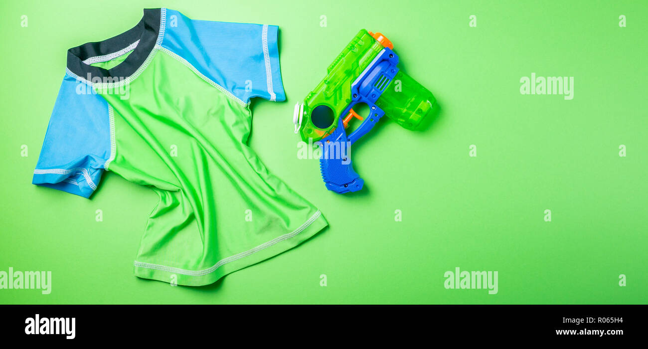 Summer fun concept - water gun and rash guard on bright background. Songkran festival, new year in thailand - Stock Image