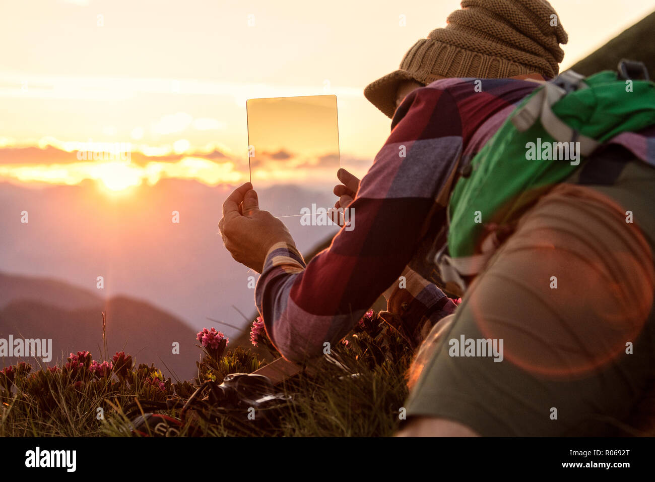 Man at sunset with graduated photography filters in his hand, San Marco Pass, Orobie Alps, Bergamo province, Lombardy, Italy, Europe - Stock Image