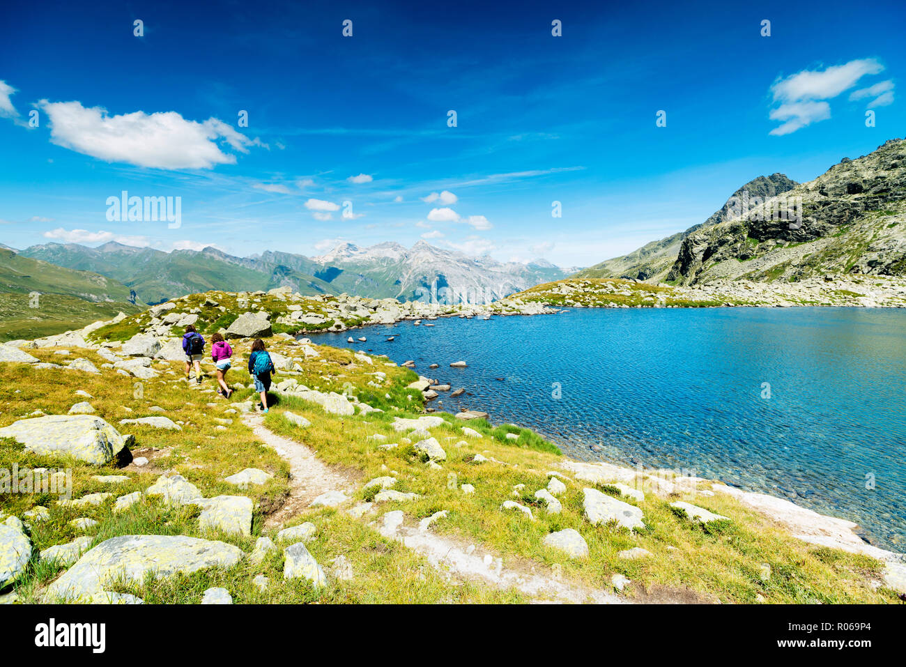 Hikers on footpath on the shore of lake Bergsee, Spluga Pass, canton of Graubunden, Switzerland, Europe - Stock Image