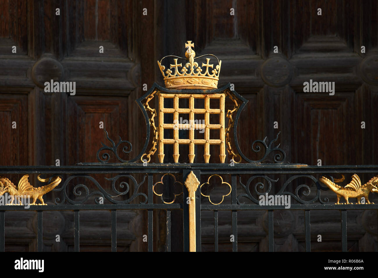 Golden painted portcullis and crown on a gate outside the west door of the tudor medieval chapel of King's college, university of Cambridge, England. - Stock Image