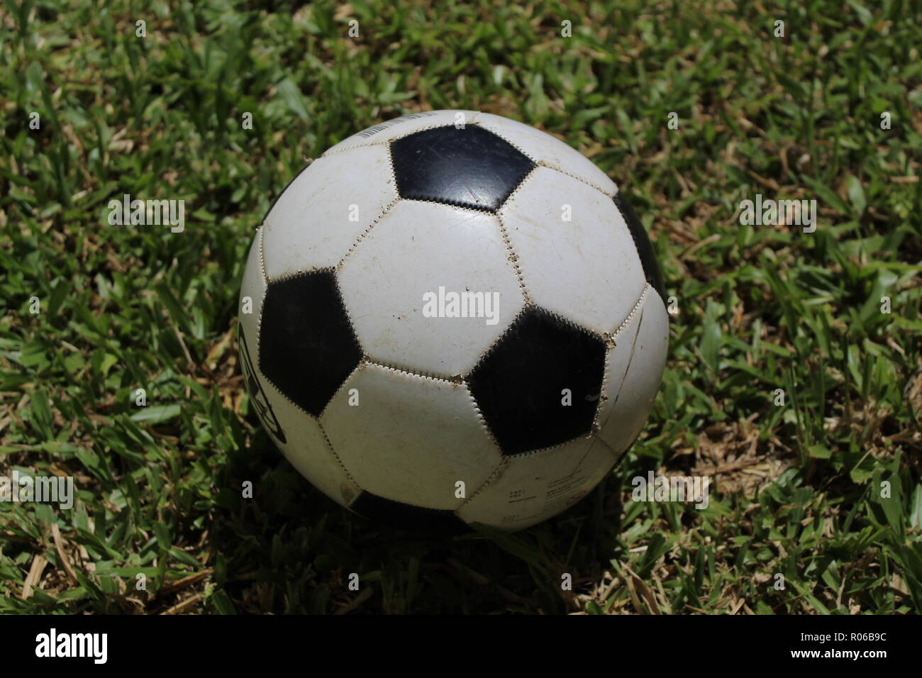 Worn ball on soccer field - Stock Image