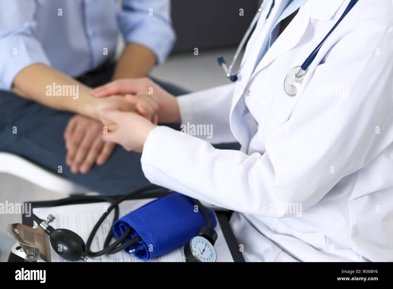 Female doctor checking blood pressure or pulse of the male patient, in hospital. Medicine and healthcare concept - Stock Image