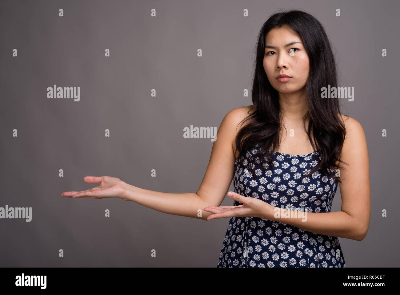 Asian woman wearing blue dress against gray background - Stock Image