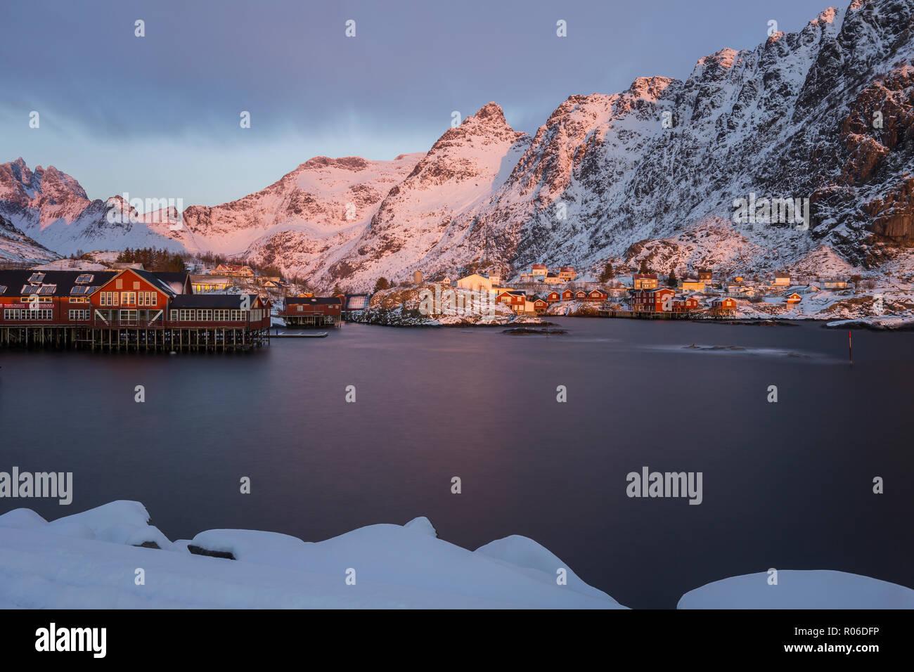 Harbor, rorbuer and snowy mountains at sunrise in Å, Moskenesøya, Lofoten, Norway - Stock Image