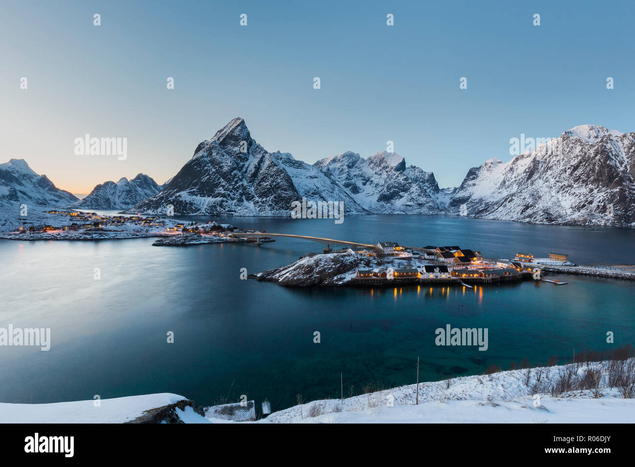 Twilight landscape with illuminated fisherman's cabins at the Sakrisøy Rorbuer in Lofoten, Norway. Winter  scenery with snow-covered mountains. - Stock Image