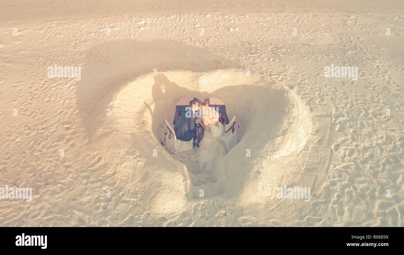 Aerial view of beach wedding. Drone photography of a lovely wedding couple. Heart shape in the sand, sunset mood - Stock Image