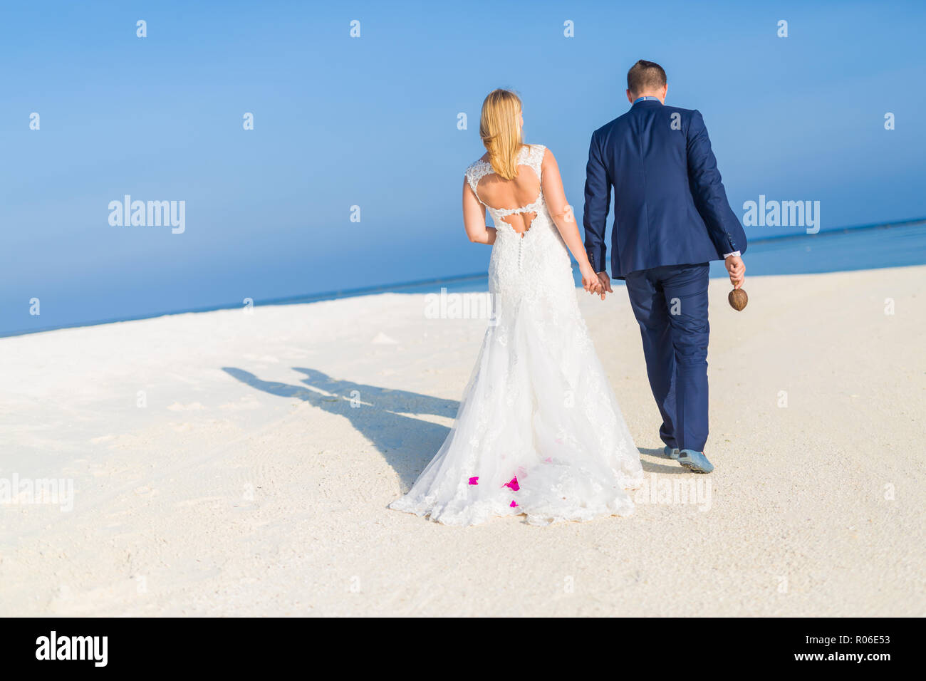 Perfect beach wedding, newlyweds couple, honeymooners. Sunset and love mood. The bride and groom under archway on beach. Romantic sunset, twilight Stock Photo