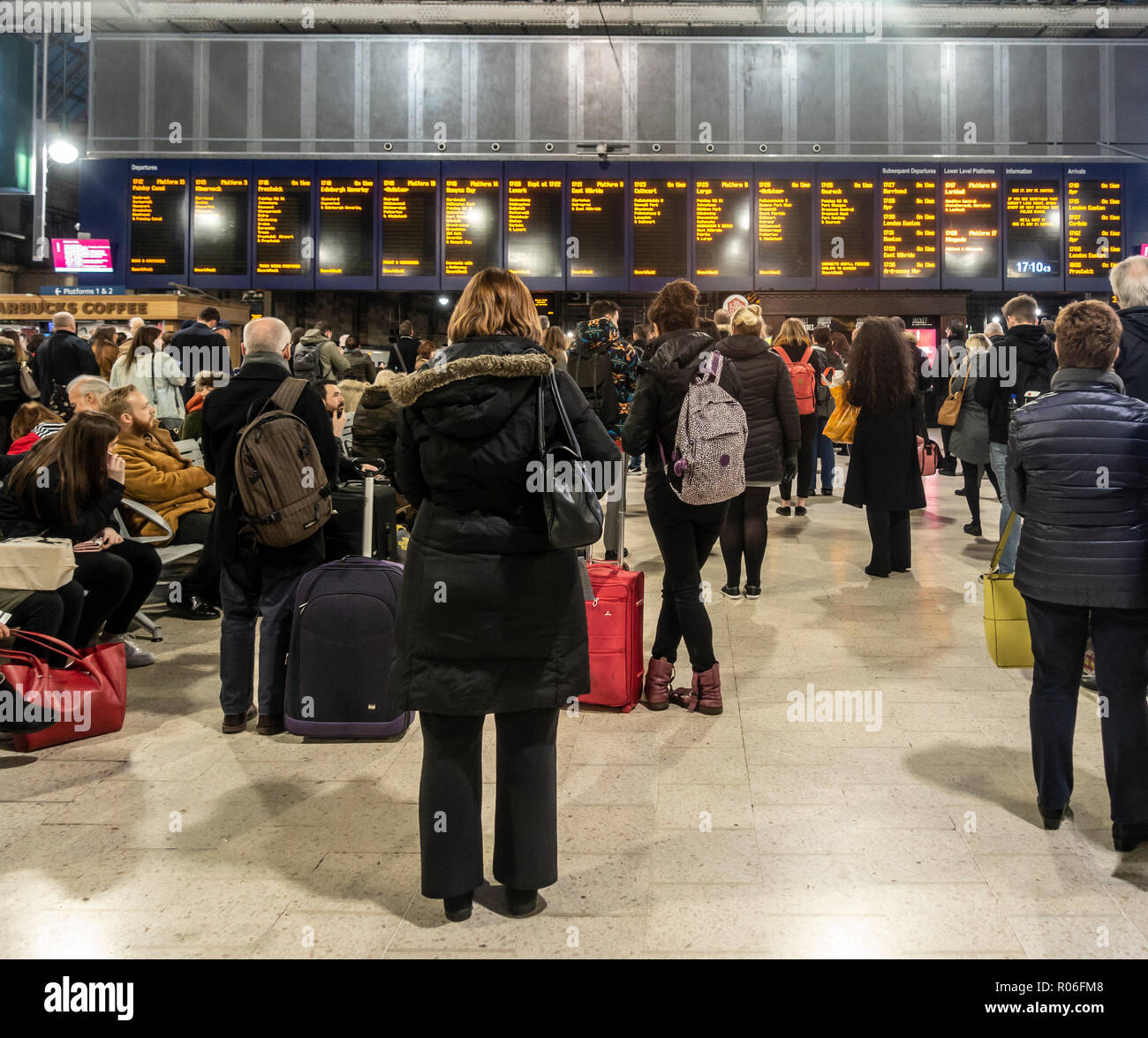 Passengers, men and women, waiting for trains and looking at the departures board on the concourse of Glasgow Central Station, Scotland, UK - Stock Image