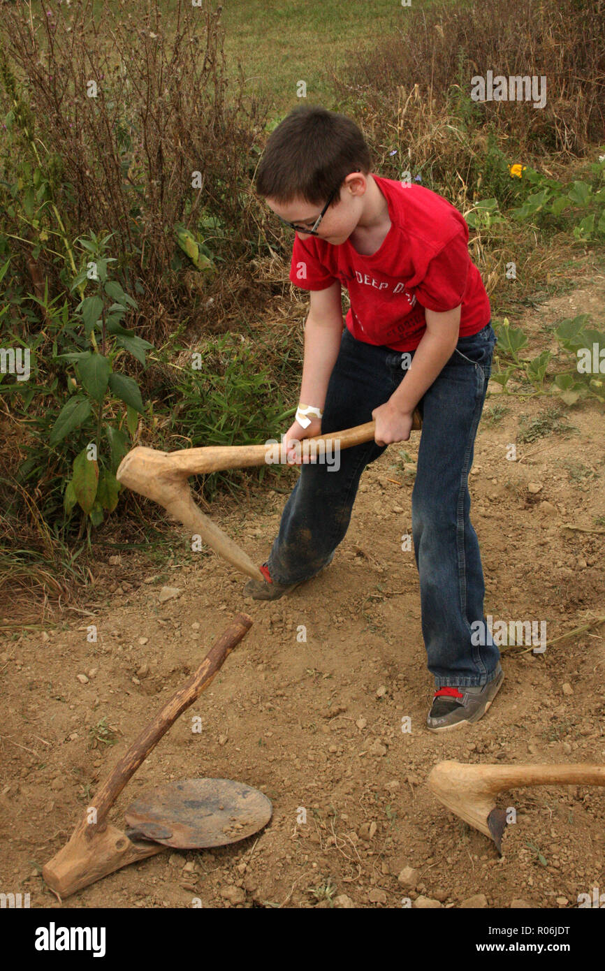 Boy trying to use a primitive wooden hoe for breaking up soil. Ancient tools at the Frontier Culture Museum in Staunton, VA. - Stock Image