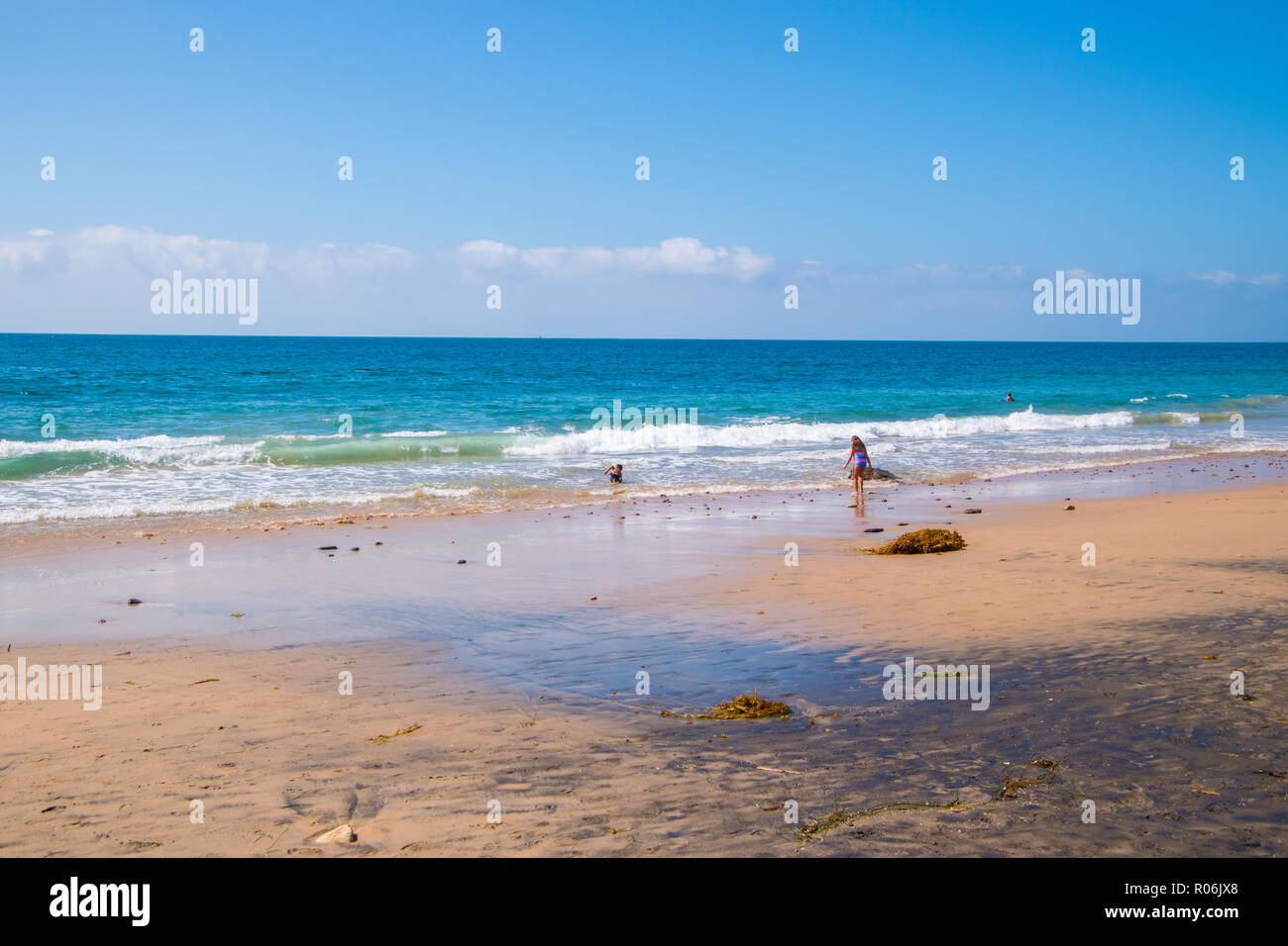 Crystal Cove, California - October 7, 2018: Beautiful flat beach with two children playing in the blue ocean as seen on this date - Stock Image