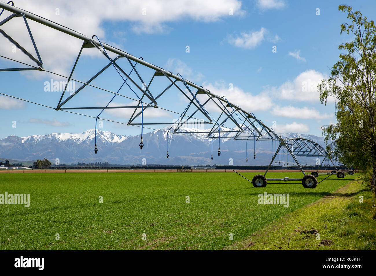 A central pivot irrigator set up on a rural farm in a large field ready to irrigate crops in springtime in New Zealand - Stock Image