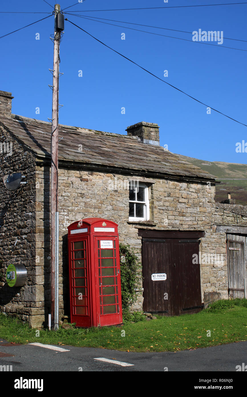 Iconic red telephone box in front of traditional stone building in Thwaite, a small village in Swaledale, Yorkshire Dales, North Yorkshire, England UK - Stock Image