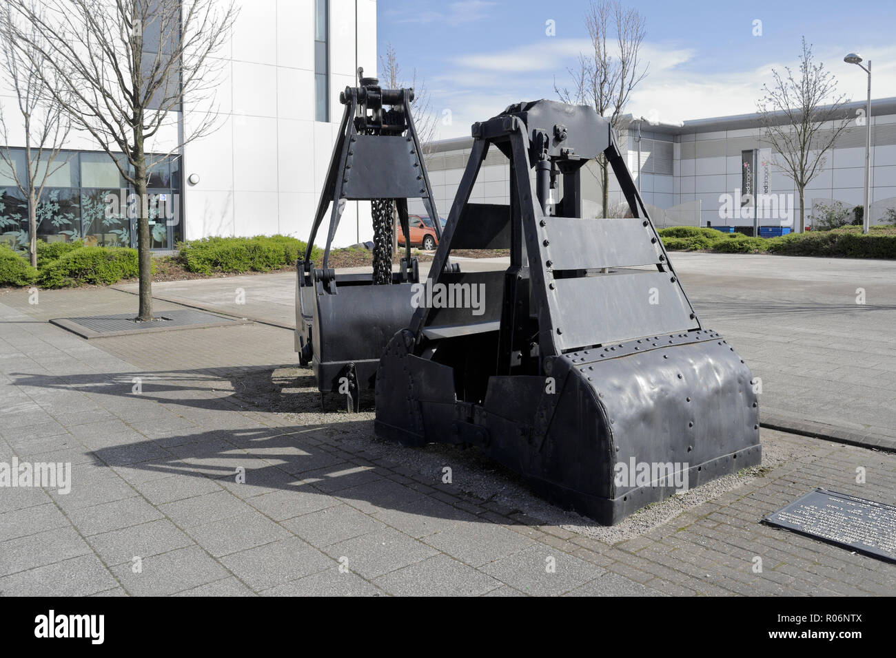 Crane coal grabs, public display of old dock machinery, Cardiff Bay Wales UK - Stock Image
