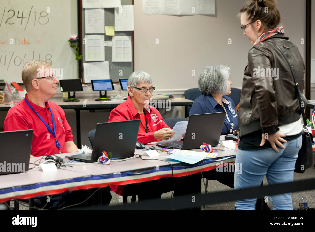 Woman waits to receive ballot while midterm poll worker (election officer) verifies identity of voter during 2018 midterm elections - Virginia USA - Stock Image